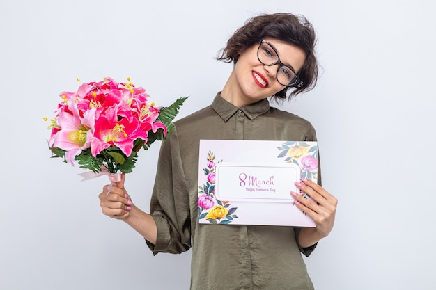 Donna con i capelli corti che tiene in mano un biglietto di auguri e un mazzo di fiori che sorride allegramente celebrando la giornata internazionale della donna l'8 marzo