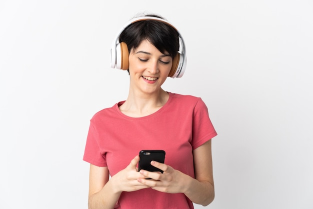 Donna con i capelli corti sopra la musica d'ascolto isolata e guardando al cellulare