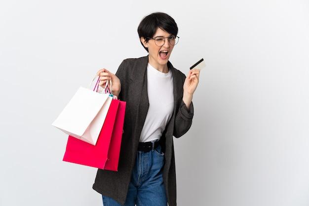 Donna con i capelli corti sopra la parete isolata che tiene i sacchetti della spesa e una carta di credito