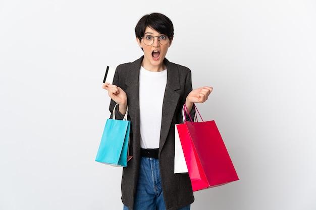 Donna con i capelli corti sopra la parete isolata che tiene i sacchetti della spesa e sorpresi