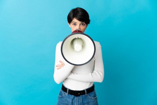 Donna con i capelli corti sopra la parete isolata che grida tramite un megafono per annunciare qualcosa