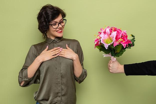 Donna con i capelli corti che sembra soddisfatta e felice mentre riceve un mazzo di fiori dal suo ragazzo che celebra la giornata internazionale della donna l'8 marzo in piedi su sfondo verde