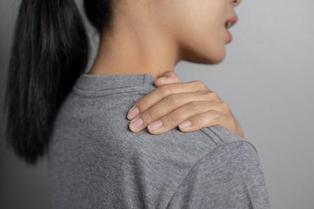 Donna con dolore alla spalla. giovane donna con dolore alla spalla. soffrendo di dolore alla spalla della donna.