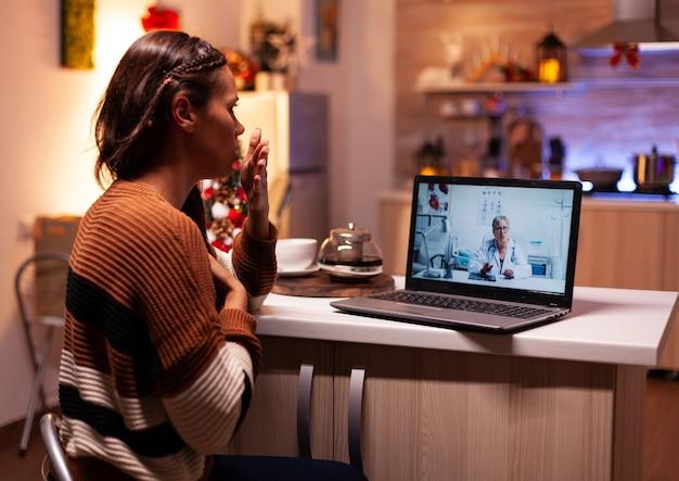 Donna malata che chiama il medico in videoconferenza online