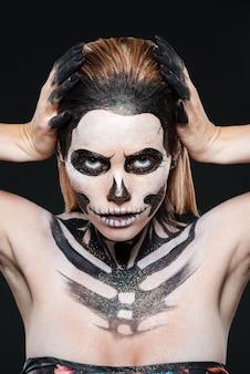 Donna con trucco di halloween scheletro su sfondo nero