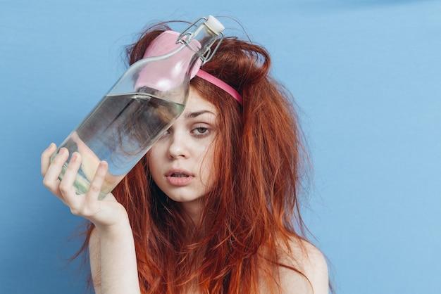 Donna con la maschera di sonno sbornia bottiglia di alcol nelle mani
