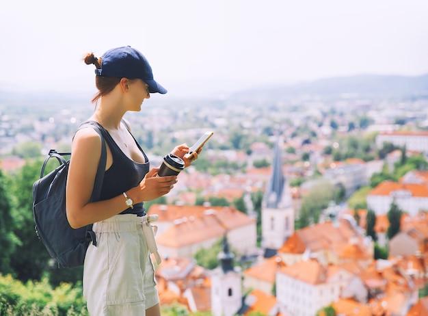 Donna con smartphone e caffè in mano sullo sfondo della vista della città con i tetti rossi di lubiana