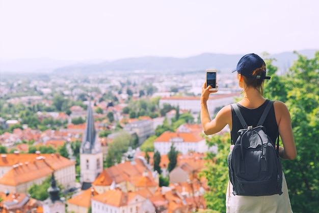 Donna con lo smartphone in mano sullo sfondo della vista panoramica con i tetti rossi della città di lubiana