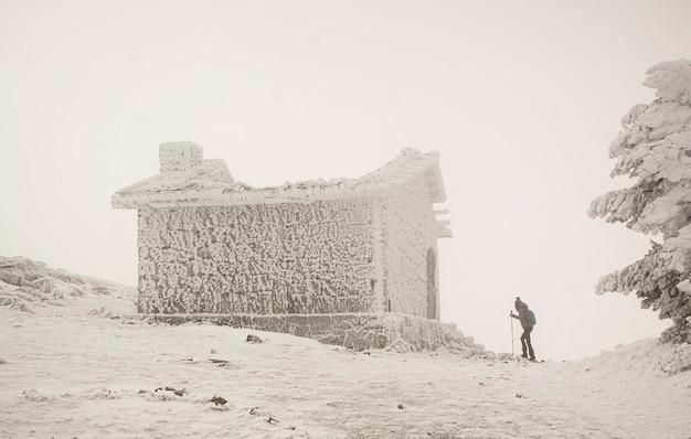 Donna con le ciaspole entrando in una baita di montagna. tempesta di neve in condizioni meteorologiche estreme. nel parco nazionale della sierra de guadarrama