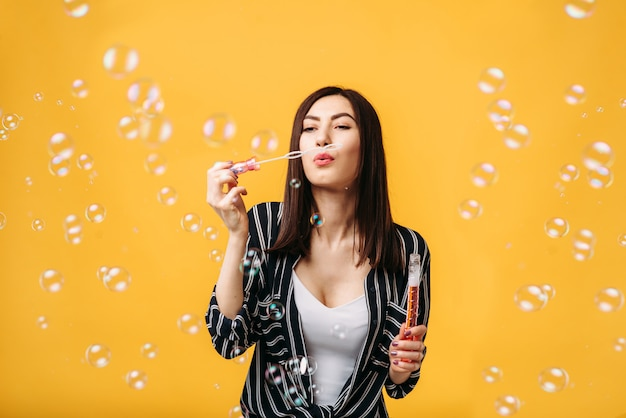 Donna con bolle di sapone, parete gialla