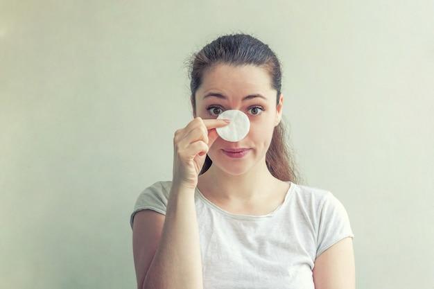 Donna con pelle morbida e sana che rimuove il trucco con un batuffolo di cotone isolato su sfondo bianco