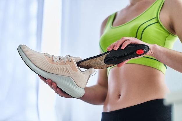 Donna con morbide solette ortopediche e scarpe da ginnastica
