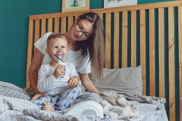 Donna con figlio che fa l'inalazione con il nebulizzatore nella loro camera da letto a casa