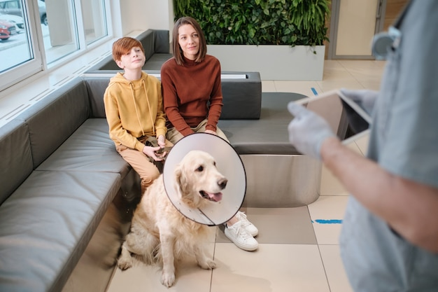 La donna con il figlio e con il loro cane ha una consultazione con il veterinario in clinica