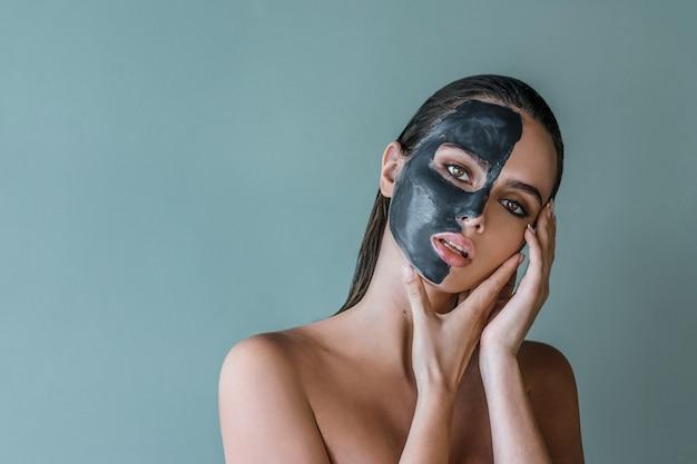 Donna con bellezza mezza faccia maschera all'argilla termale. ritratto sano concetto su uno sfondo di studio.