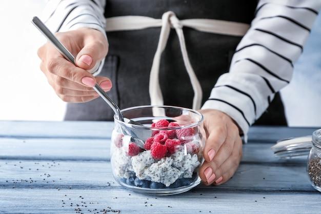 Donna con cucchiaio e vasetto di delizioso budino di semi di chia a tavola