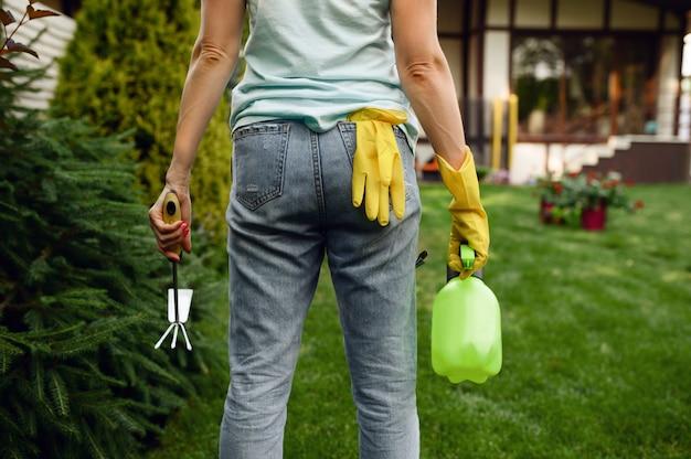 Donna con spray e zappa in giardino, vista posteriore. il giardiniere femminile si prende cura delle piante all'aperto, dell'hobby del giardinaggio, dello stile di vita del fiorista e del tempo libero