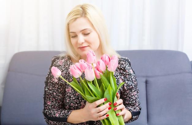 Donna con bouquet di fiori di primavera. felice modello sorpreso donna annusare i fiori. festa della mamma. primavera