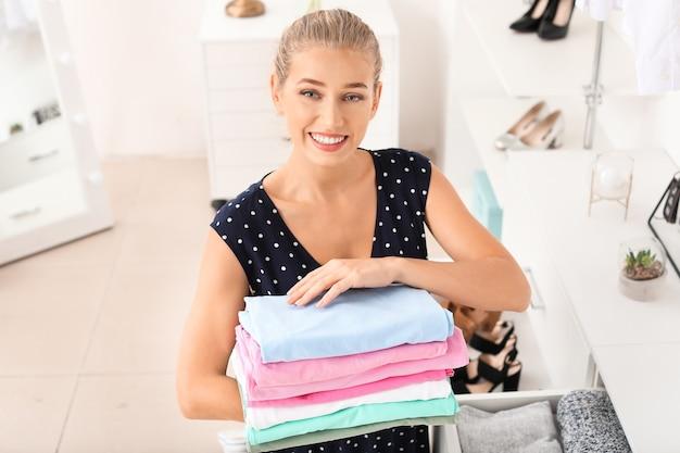 Donna con una pila di vestiti puliti a casa