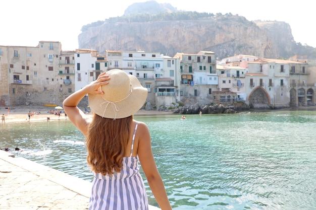 Donna con cappello di paglia e abito a righe con il villaggio di cefalù sullo sfondo, mar mediterraneo, sicilia
