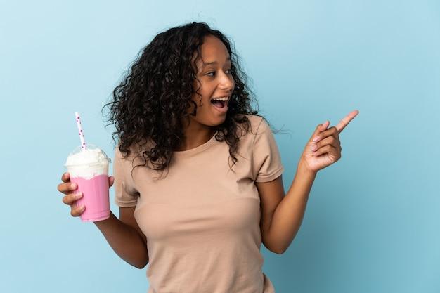 Donna con frappè alla fragola isolato su blu che intende realizzare la soluzione mentre solleva un dito
