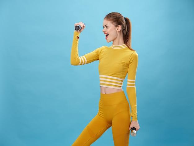 Una donna con una tuta elegante fa sport e fa esercizi, una tuta gialla, uno spazio blu