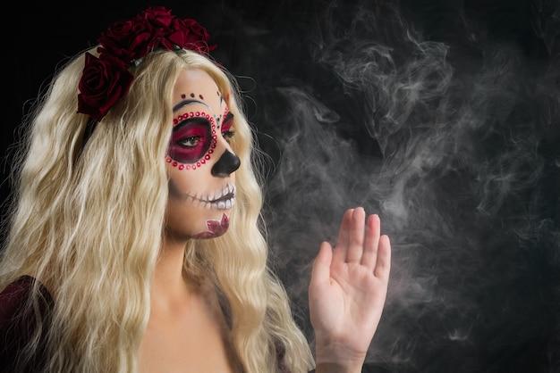 Donna con trucco del cranio dello zucchero e capelli biondi isolati su priorità bassa nera. giorno della morte. halloween. copia spazio.