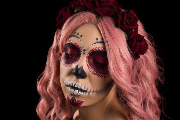 Donna con trucco del cranio dello zucchero e capelli rosa isolati