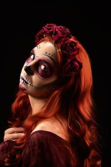 Donna con trucco del cranio dello zucchero e capelli rossi isolati
