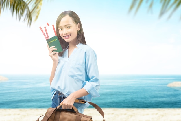 Donna con una valigia con biglietto e passaporto sulla spiaggia
