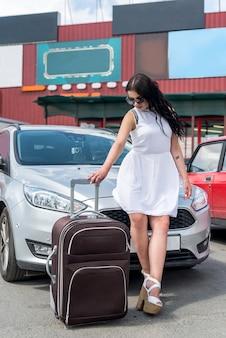 Donna con valigia seduta sul cofano dell'auto