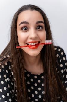 La donna con gli occhi sorpresi tiene lo spazzolino orizzontalmente in bocca. emozioni divertenti.