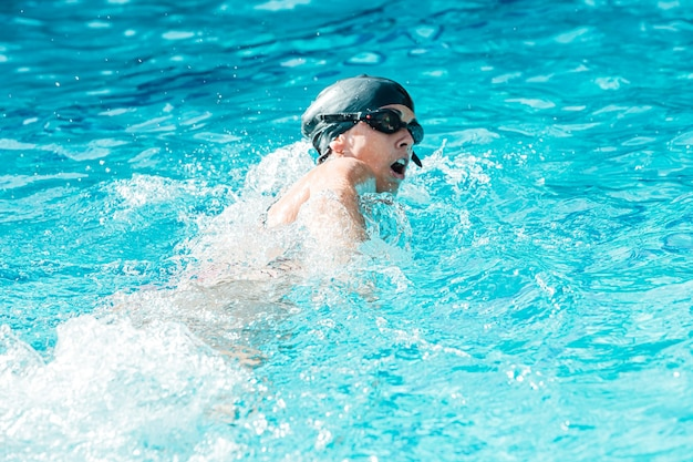 Donna con cuffia e occhiali per nuotare in una piscina