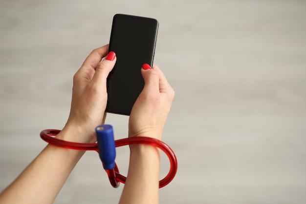 Donna con le mani legate che tengono il primo piano del telefono cellulare
