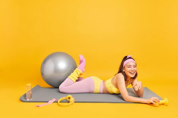 La donna con l'espressione felice stanca giace sul tappetino fitness circondata da attrezzature sportive vestite con abiti sportivi