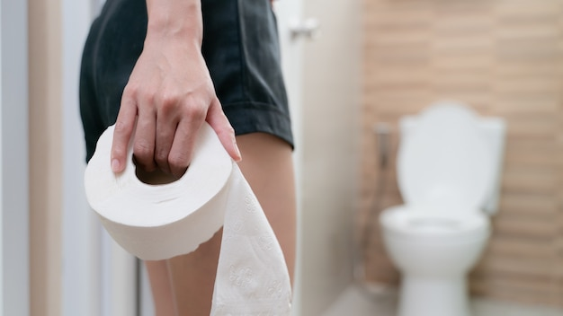 Donna con carta igienica, sintomi di diarrea mal di stomaco, crampi mestruali o intossicazione alimentare. concetto di assistenza sanitaria.