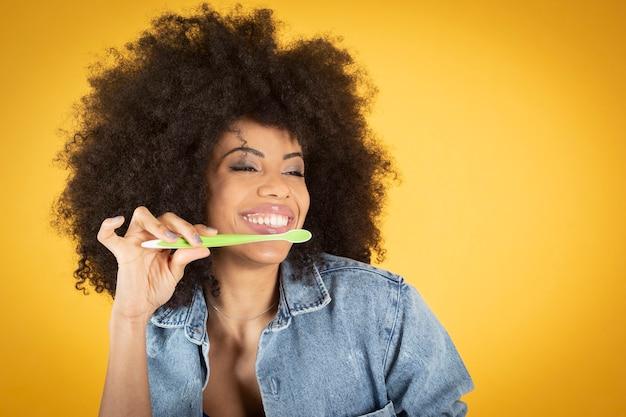 Donna con spazzolino da denti, denti bianchi, donna africana piuttosto mista, con capelli afro, sorridente, sfondo giallo