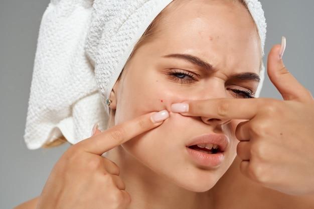 Donna con l'asciugamano sul primo piano facciale delle spalle nude della testa