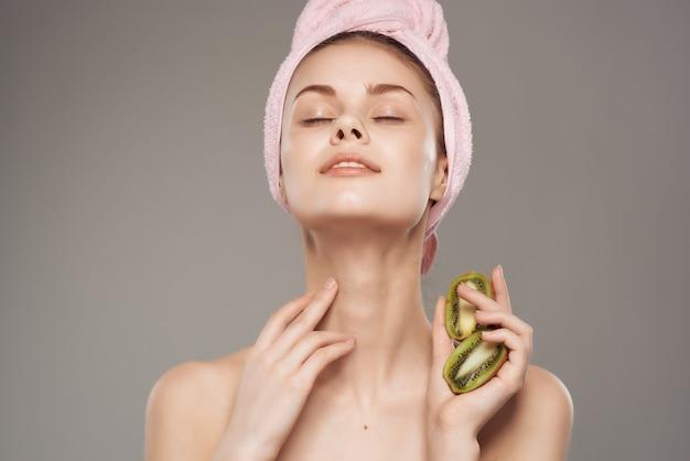 Donna con un asciugamano sulla testa dopo la doccia kiwi in mano vista ritagliata