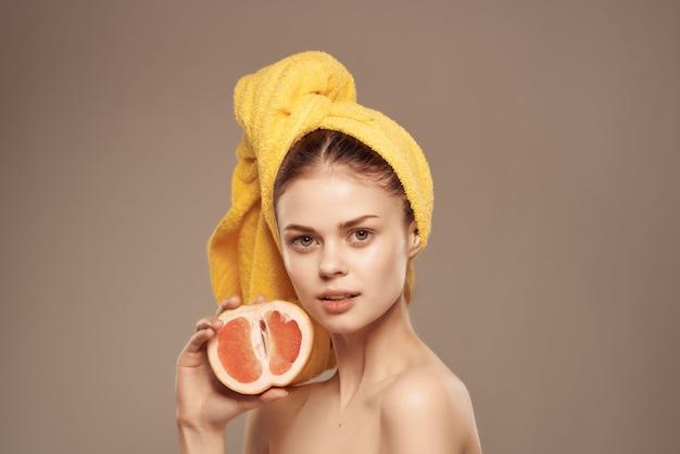 Donna con un asciugamano sulla testa, pelle pulita, pompelmo in mano, vista ritagliata