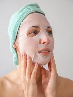 Una donna con un asciugamano in testa e una maschera sul viso