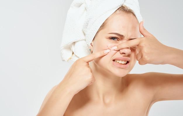 Una donna con un asciugamano sulla testa spreme l'acne sulla sua dermatologia cosmetologica della pelle del problema del viso