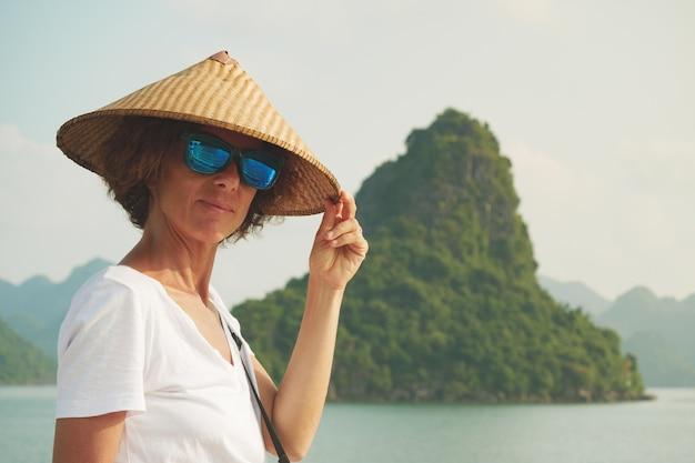 Donna con il tradizionale cappello vietnamita guardando la vista unica della baia di halong in vietnam