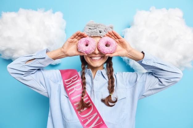 Donna con due treccine ha espressioni allegre contro occhi con deliziose ciambelle glassate come se gli occhiali si divertissero il giorno del compleanno indossa abiti casual pose contro il blu