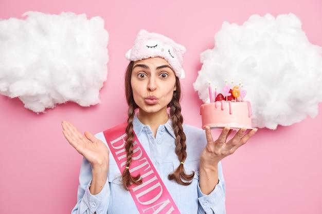 Donna con due codini tiene le labbra piegate tiene la torta festiva festeggia il compleanno indossa una camicia casual con maschera da notte isolata sul rosa