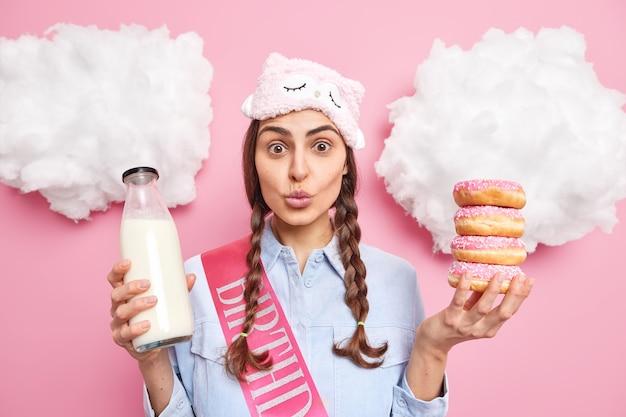 Donna con due codini tiene le labbra arrotondate fa uno spuntino tiene una pila di ciambelle glassate e una bottiglia di latte indossa una maschera per dormire abiti casual passa il tempo a casa