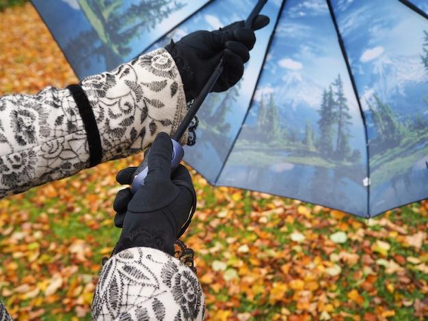 Donna con l'ombrello nel parco di autunno.