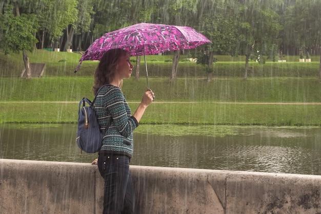 Donna con un ombrello in natura sotto la pioggia estiva