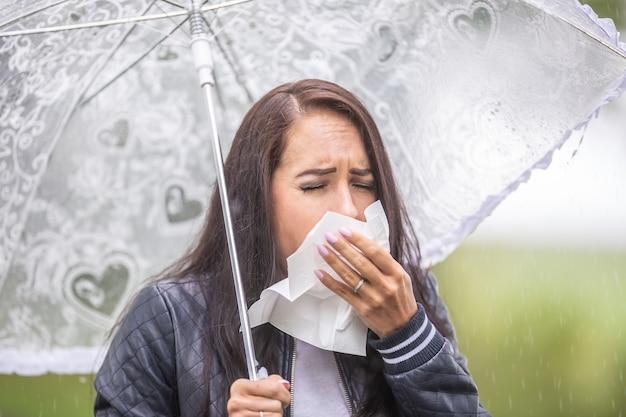 La donna con un ombrello all'aperto starnutisce in un tovagliolo, raffreddandosi a causa del maltempo.