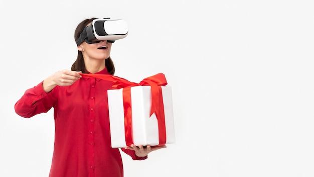 Donna con la confezione regalo della holding della cuffia avricolare di realtà virtuale
